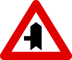 Traffic sign of Belgium: Warning for a crossroad with a side road on the left